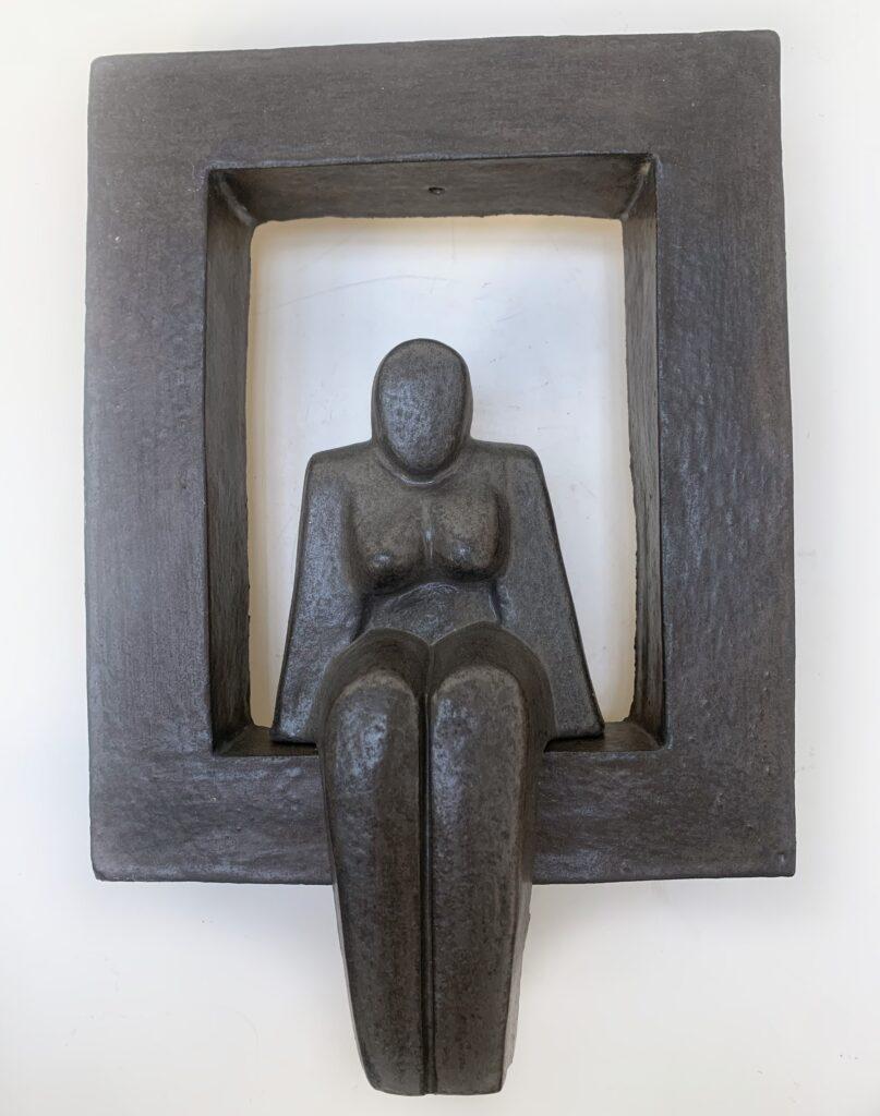 Zittende vrouw in kader – keramiek