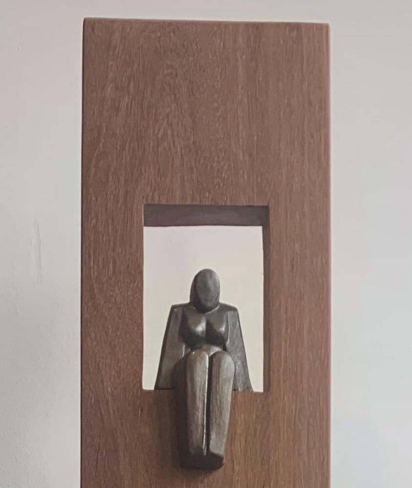 Zittende vrouw (keramiek) in houten zuil